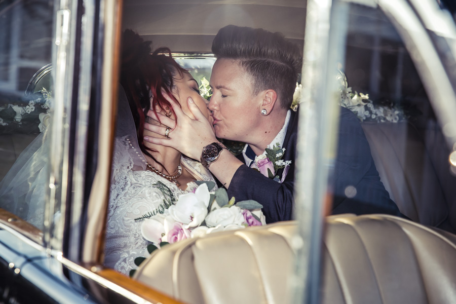 Same-sex-wedding-couple-kissing-in-an-old-vintage-car